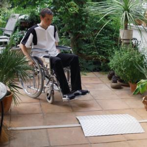 Rollstuhlfahrer vor eine Schwellenrampe