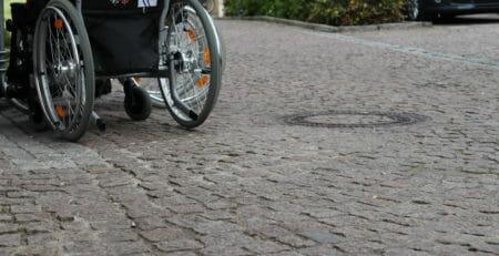 Rollstuhlrad auf Kopfsteinpflaster