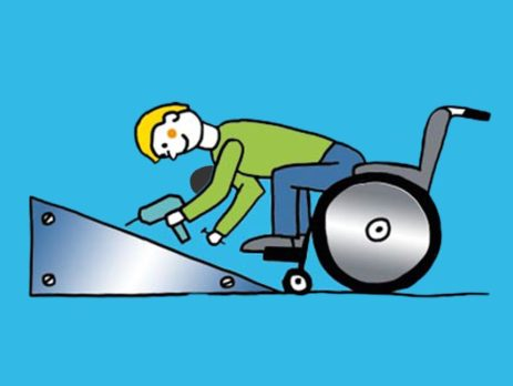 Rollstuhlfahrer schraubt Rampe fest.